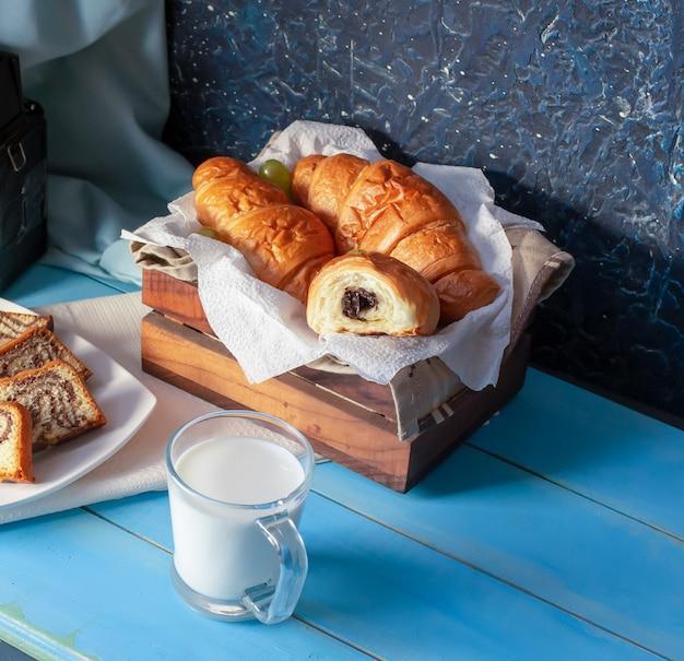 Croissants à la crème au chocolat et une tasse de lait.