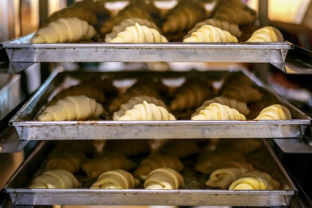 Croissants crus faits maison sur une plaque à pâtisserie cuits au four