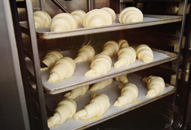 Croissants crus préparés pour une cuisson au four en gros plan
