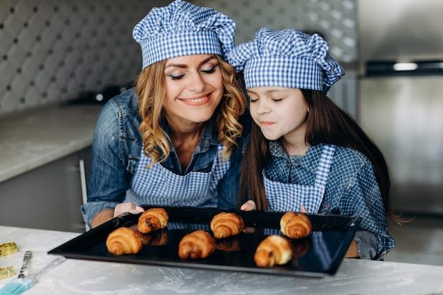 Des croissants cuits au four par la fille et la mère en inhalent l'odeur. concept de famille
