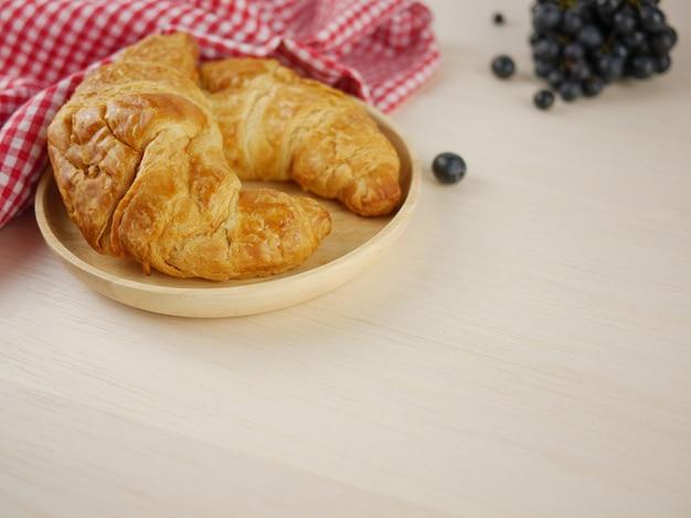 Croissants dans une assiette en bois avec espace de copie