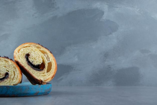 Croissants demi-coupés au chocolat sur plaque bleue.