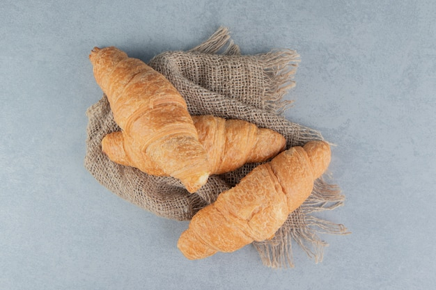 Croissants dentelés sur une serviette, sur le fond de marbre. photo de haute qualité