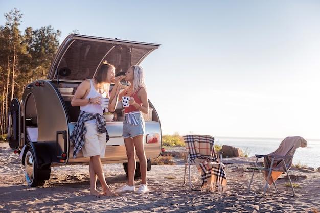 Croissants du matin. couple de voyageurs élégants et élégants vivant dans une maison mobile, manger un croissant le matin