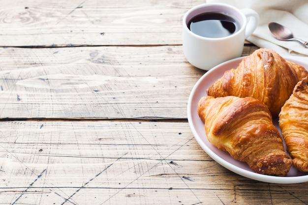 Croissants du petit déjeuner sur une assiette et une tasse de café, table en bois.