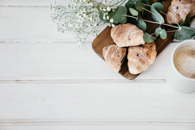 Croissants, fleurs, café et copie