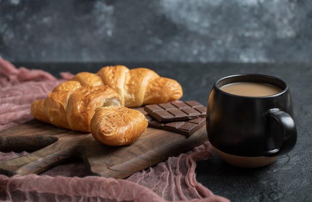 Croissants fourrés au chocolat sur une planche en bois.