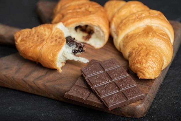 Croissants fourrés au chocolat sur une surface sombre.