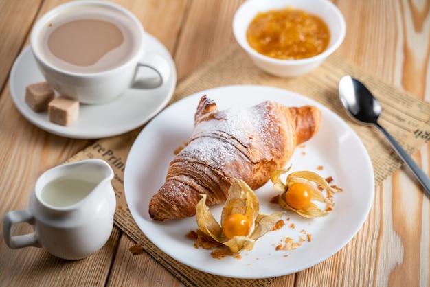 Croissants fraîchement cuits au four sur une table en bois gris, vue du dessus