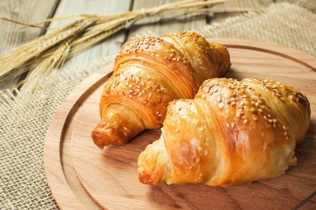 Croissants fraîchement cuits sur une planche à découper en bois, vue de dessus. fait maison ou boulangerie.