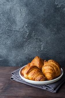 Croissants fraîchement cuits sur une plaque, fond sombre,
