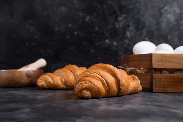 Croissants fraîchement sortis du four avec des œufs de poule et bol de farine en bois.