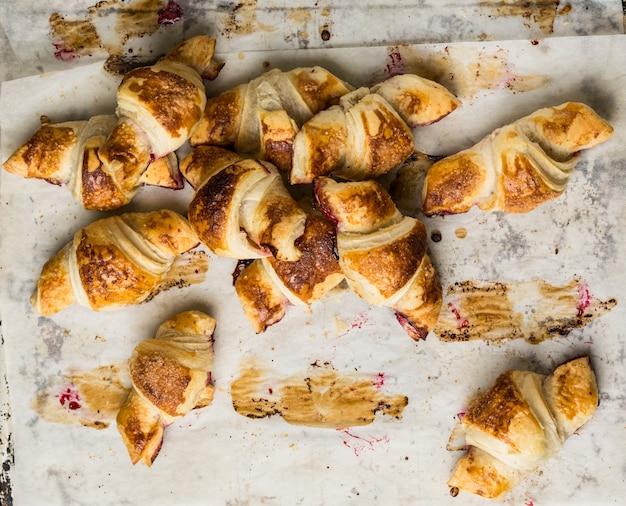 Croissants fraîchement sortis du four sur papier parchemin, vue de dessus.