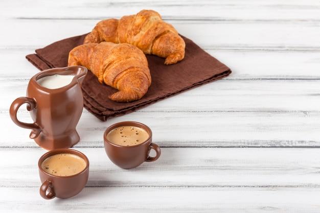 Des croissants fraîchement sortis du four sur une serviette brune, de la crème, à des tasses de café dans des plats en céramique sur un fond en bois blanc. pâtisseries fraîches pour le petit déjeuner. dessert délicieux. photographie gros plan. bannière horizontale