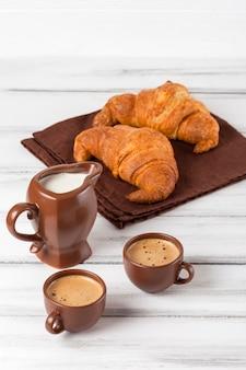 Des croissants fraîchement sortis du four sur une serviette brune, de la crème, à des tasses de café dans des plats en céramique sur un fond en bois blanc. pâtisseries fraîches pour le petit déjeuner. dessert délicieux. photographie gros plan. bannière verticale.