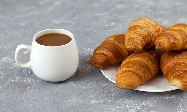Croissants fraîchement sortis du four et tasse de café sur une table en pierre rustique