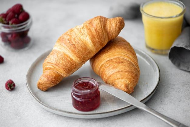 Croissants frais croquants avec confiture de framboises et jus d'orange sur une table grise