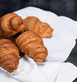 Croissants frais cuits au four sur une serviette en tissu blanc