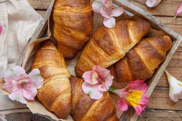 Croissants frais et fleurs dans un bac sur une vue de dessus de table en bois