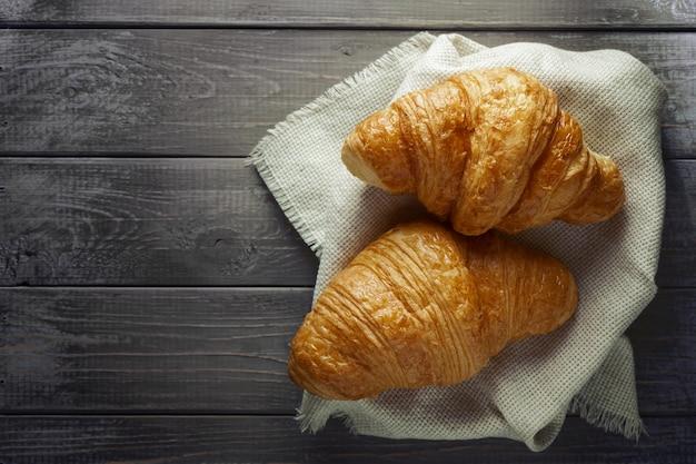 Croissants frais sur fond de bois ancien. style rustique. lay plat, espace de copie.