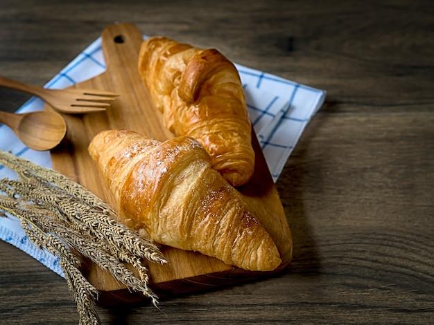Croissants frais petit déjeuner décoré avec de l'herbe de blé sur la table en bois