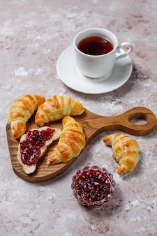 Des croissants frais et savoureux faits maison avec de la confiture de framboises sur du gris-blanc. patisserie française
