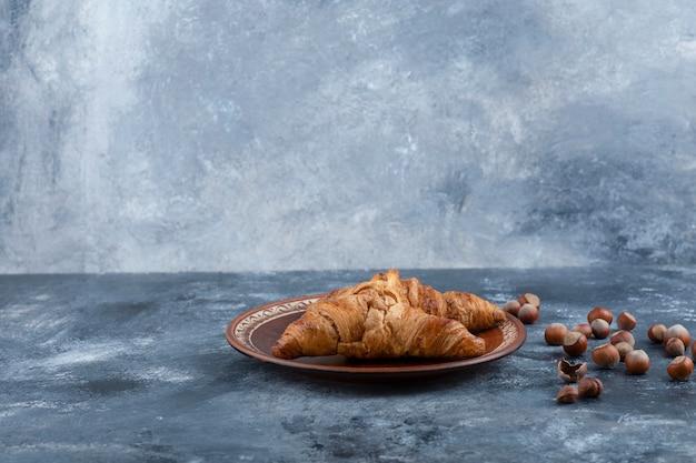 Croissants frais et savoureux avec des noisettes saines en coque.