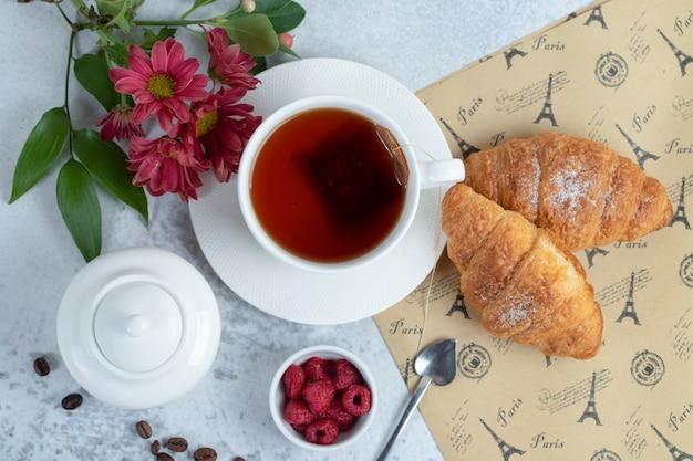 Croissants frais avec une tasse de thé et des fruits sucrés.
