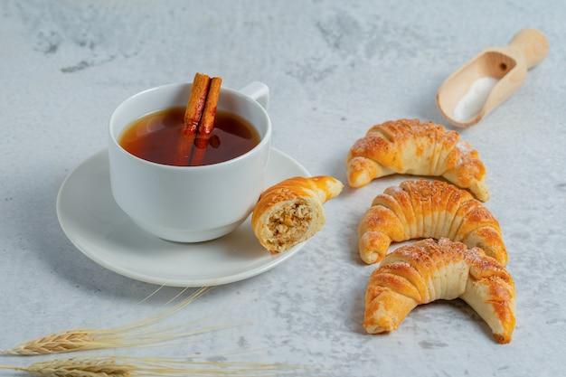 Croissants frais avec thé parfumé sur surface grise.