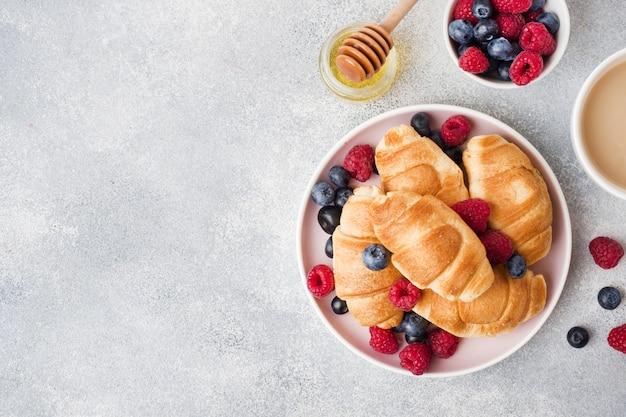 Croissants avec framboises et bleuets frais sur une surface de béton grise