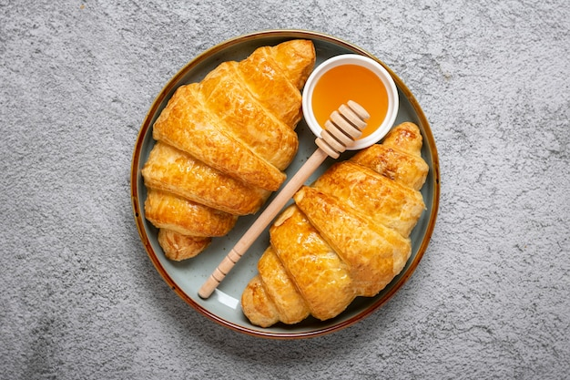 Croissants français frais au chocolat sur plaque, miel sur fond de granit gris continental