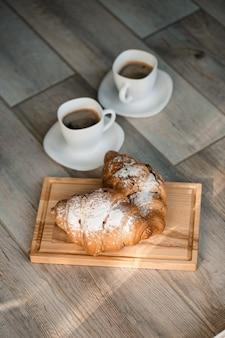 Croissants de pâtisseries fraîches au chocolat sur une planche en bois et deux tasses de café noir. petit déjeuner romantique