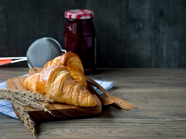 Croissants sur la planche de bois avec pot de confiture de fraises et passoire sur la table en bois