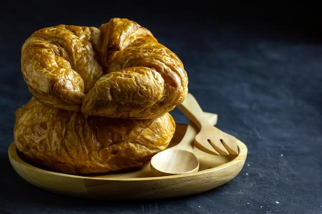 Croissants sur plat en bois et cuillère en bois et une fourchette sur la table dans un fond sombre.