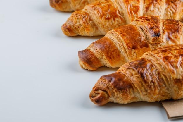Croissants sur sac blanc et papier, gros plan.