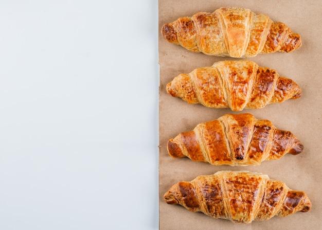 Croissants sur sac blanc et papier, pose à plat.
