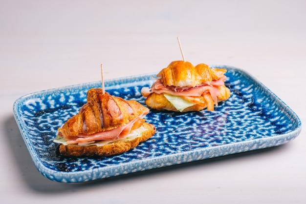 Croissants et sandwichs avec diverses garnitures, fromage, jambon de parme et salade