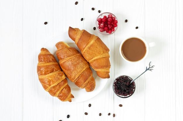Croissants savoureux avec des baies, de la confiture et une tasse de café vue de dessus. concept de petit-déjeuner du matin
