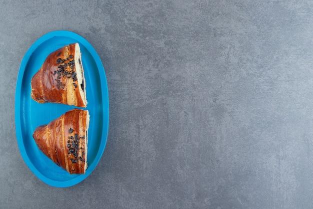 Croissants savoureux à moitié coupés au chocolat sur plaque bleue.