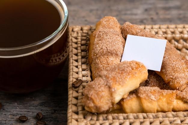 Croissants se trouvent dans un panier en osier avec tasse de thé