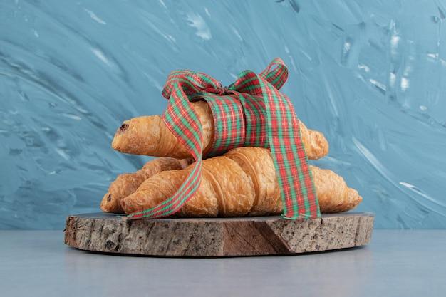 Croissants sucrés sur le plateau, sur le fond bleu. photo de haute qualité