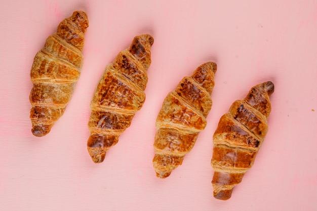 Croissants sur une table rose. pose à plat.