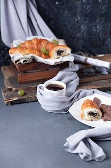 Croissants avec une tasse d'espresso sur la table bleue