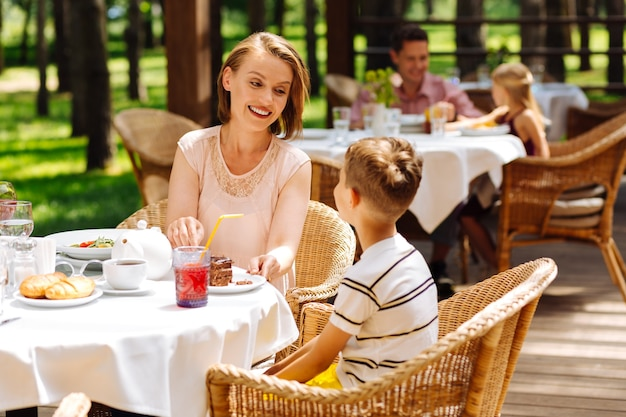 Croissants et thé. mère souriante attentionnée se sentant incroyable tout en traitant son fils avec des croissants et du thé