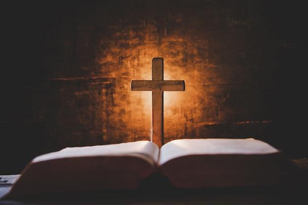 Croix avec bible et bougie sur une vieille table en bois de chêne.