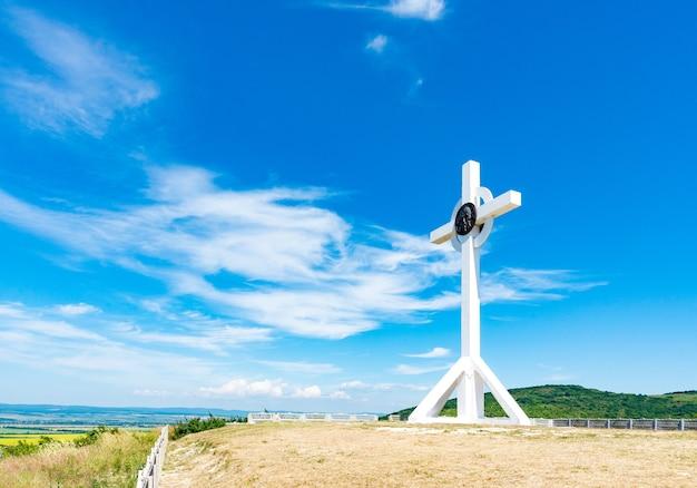 Une croix en bois au sommet d'une colline. la croix blanche orthodoxe brille au sommet de la colline sur fond de ciel bleu et d'herbe verte.