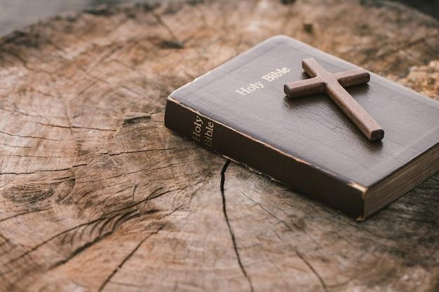 Une croix en bois sur la sainte bible sur une table en bois lectures du dimanche éducation biblique