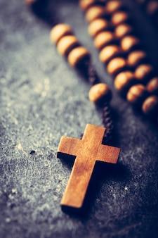 Croix et chapelet sur fond de pierre