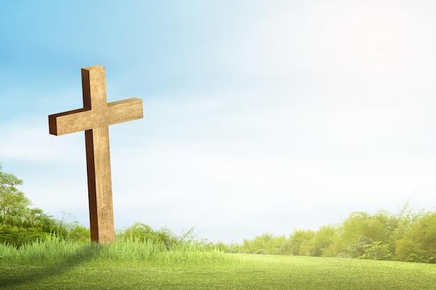 Croix chrétienne sur l'herbe verte avec la lumière du soleil