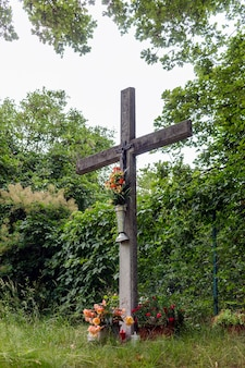 Une croix avec le christ crucifié ornée de nombreuses fleurs